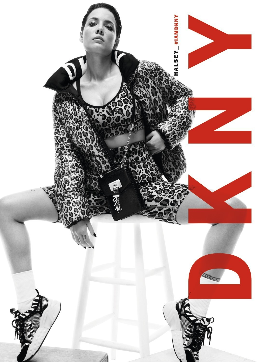 The artist Halsey, sitting on a stool with a leopard printed down jacket from the Fall 19 DKNY collection made by the Mazarine agency.