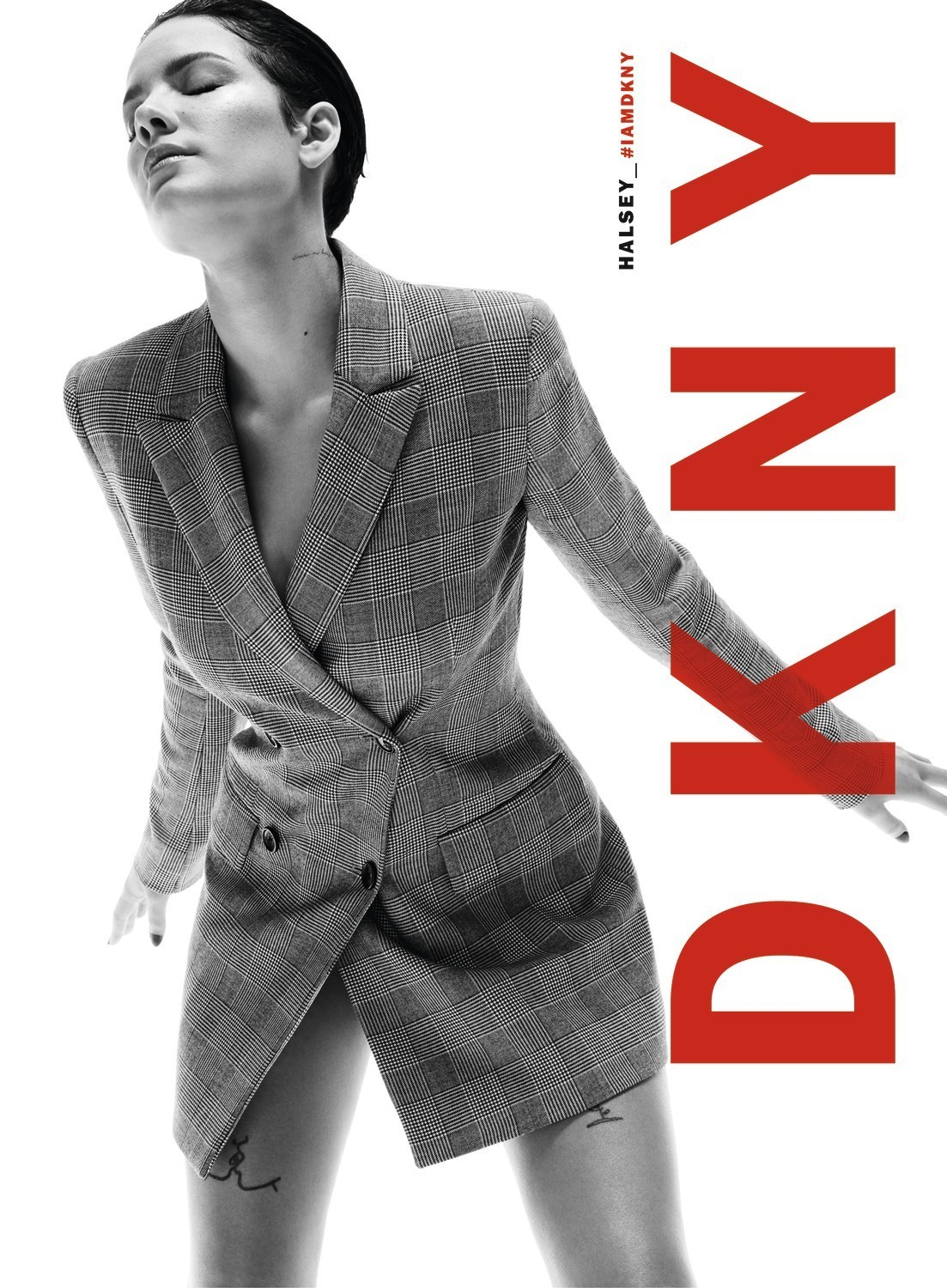Black and white advertising photograph of American singer Halsey in a DKNY checkered crossover suit for the Fall19 campaign.