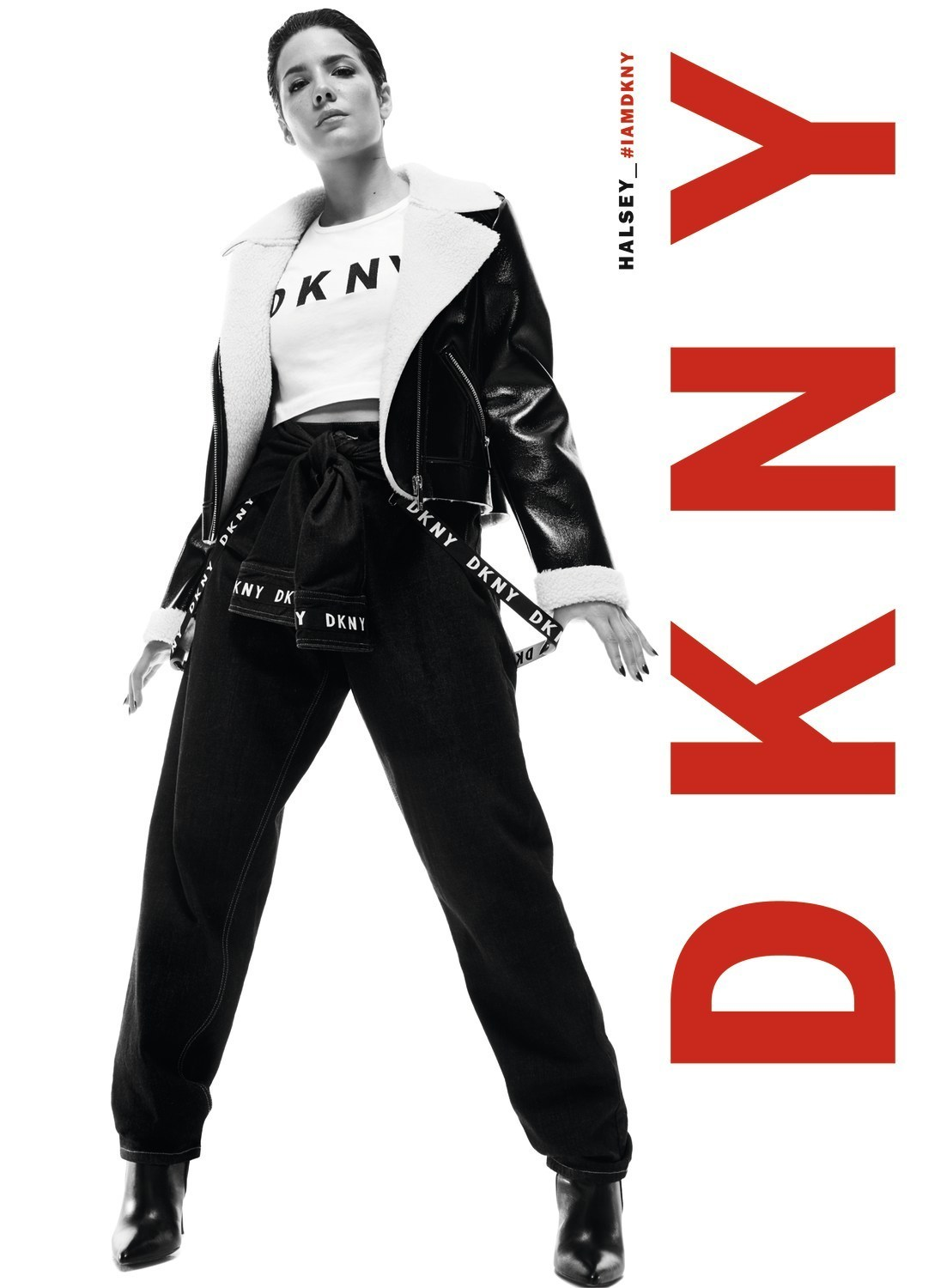 Black and white advertising photograph of the artist Halsey in black jeans, white t-shirt and aviator coat for the Fall 19 DKNY campaign.