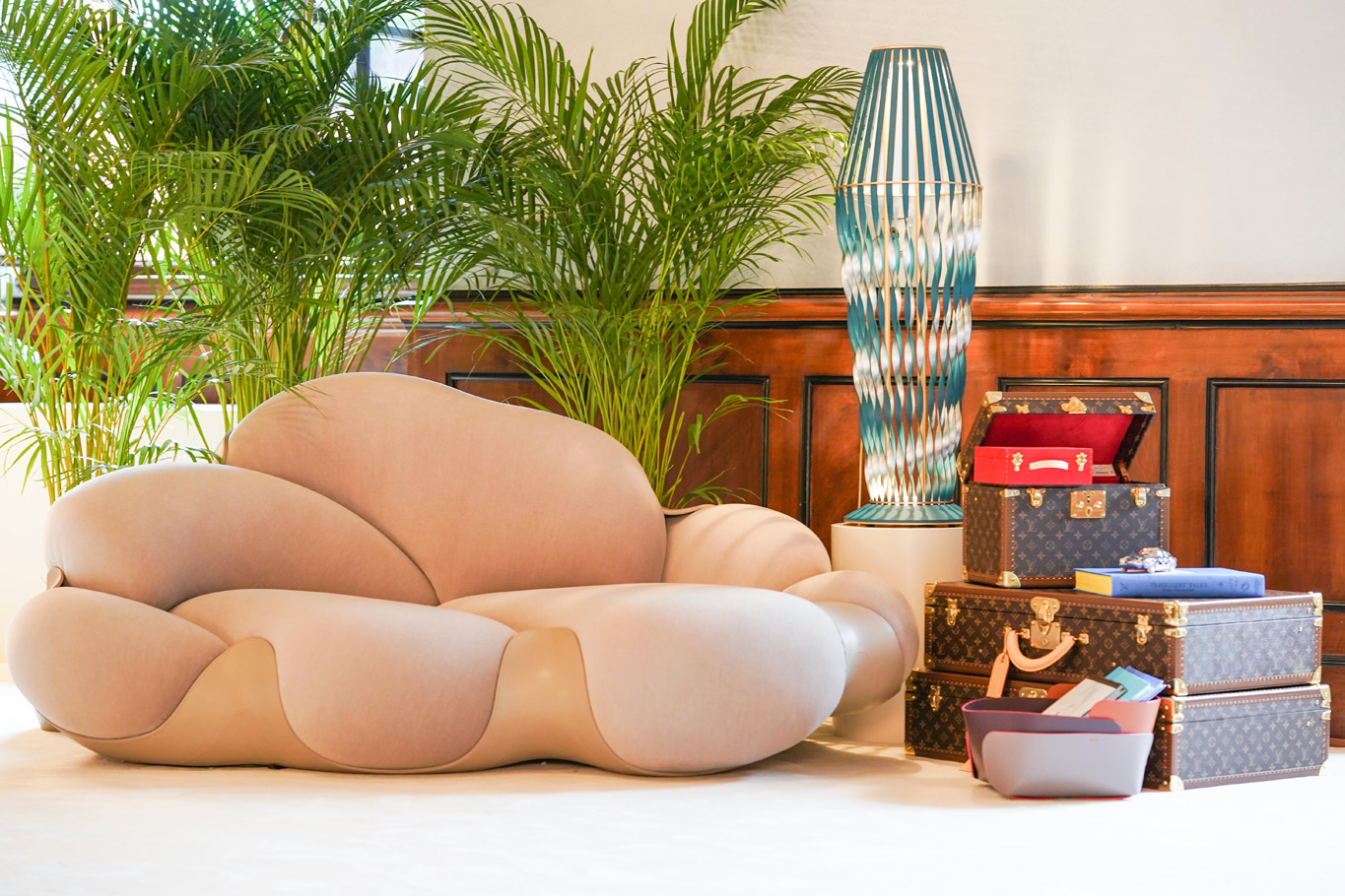 Sofa in flesh pink from the Louis Vuitton Haute Joaillerie exhibition in Shanghai with two tropical grass-green greasy plants in the background, a glass lamp with 3 Louis Vuitton trunks in the bottom right.